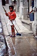 Young girl outside her home helping her mother clean the walk in Havana, Cuba