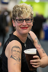 © Licensed to London News Pictures . 25/09/2015 . Doncaster , UK . KERRIE WEBB (38) from Chesterfield , tips her pint of beer towards her Nigel Farage Tattoo at the 2015 UKIP Party Conference at Doncaster Racecourse , this afternoon (Friday 25th September 2015) . Photo credit : Joel Goodman/LNP