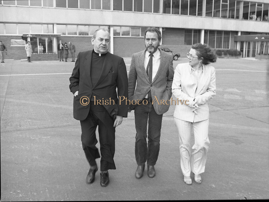Trocaire Team Departs for Ethiopia..1985..24.03.1985..03.24.1985..24th March 1985..To view the Trocaire relief project on the ground,.Cardinal Tomas O Fiaich,Chairman of Trocaire,accompanied by Mr Brian Mc Keown,Director of Trocaire and Ms Sally O'Neill,Head of Trocaire Projects departed Dublin Airport on their way to Ethiopia and Sudan. Trocaire along with many other agencies were assisting in famine relief on the African Continent..Image shows Cardinal O'Fiaich,Ms O'Neill and Mr McKeown crossing the tarmac to the waiting aircraft.