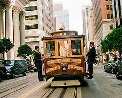 two men in suits riding on the back of the San Francisco cable car