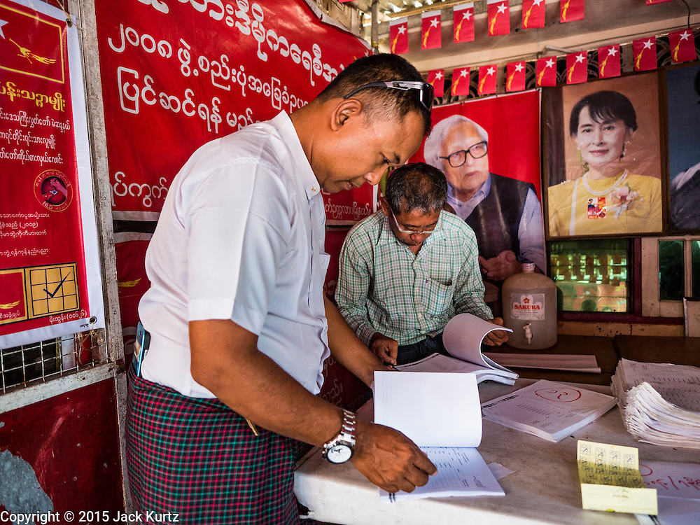 02 NOVEMBER 2015 - YANGON, MYANMAR: A Burmese voter (left) looks for his name on a list of voters at a NLD campaign outreach office in Mingaladon, a township in Yangon. Voter registration rolls were released Monday. Voters and party officials are double checking rolls to ensure accuracy.  A photo of NLD leader Aung San Suu Kyi is on the wall behind him. National elections are scheduled for Sunday Nov. 8. The two principal parties are the National League for Democracy (NLD), the party of democracy icon and Nobel Peace Prize winner Aung San Suu Kyi, and the ruling Union Solidarity and Development Party (USDP), led by incumbent President Thein Sein. There are more than 30 parties campaigning for national and local offices.     PHOTO BY JACK KURTZ