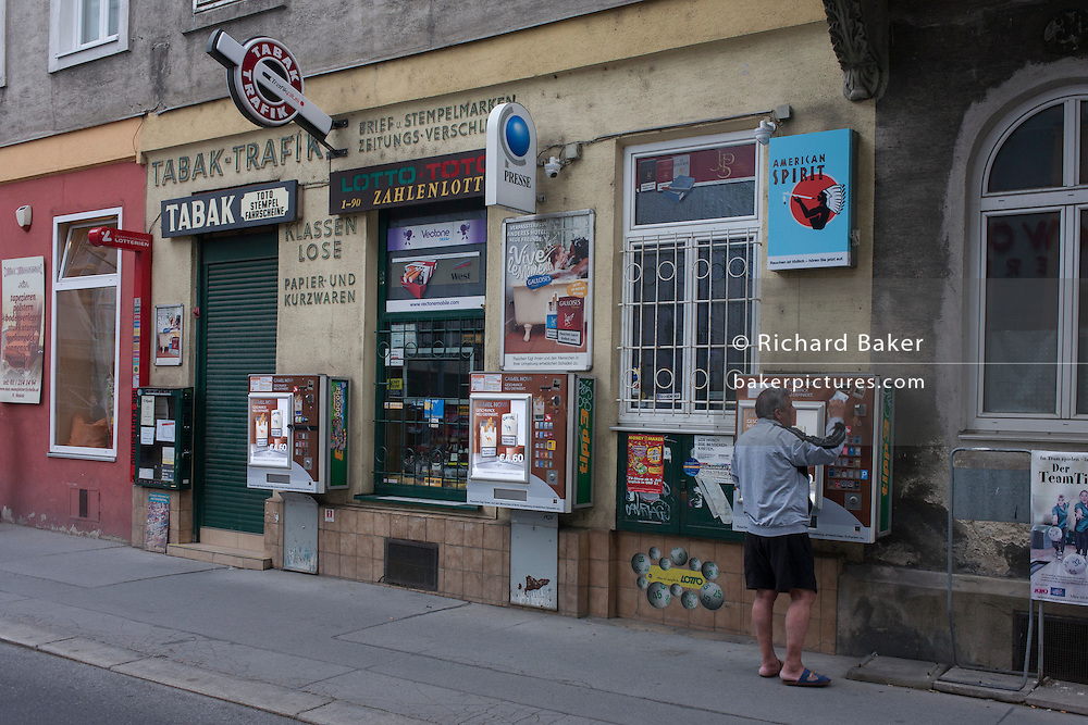 While the local Tabak is closed for the night, a smoker pays for cigarettes from a street cigarette dispenser on 26th June 2016, in Vienna, Austria. After years of debate, Austria's government has announced plans to introduce a total smoking ban in cafes and restaurants by 2018. (Photo by Richard Baker / In Pictures via Getty Images)