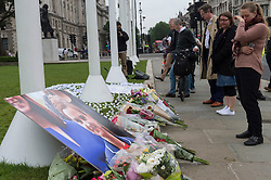 © Licensed to London News Pictures. 17/06/2016. A well wisher wipes away her tears in front of flowers and tributes in Parliament Square in memory of Labour party MP JO COX.  She was allegedly attacked and killed by suspect 52 year old Tommy Mair close to Birstall Library near Leeds.  London, UK. Photo credit: Ray Tang/LNP
