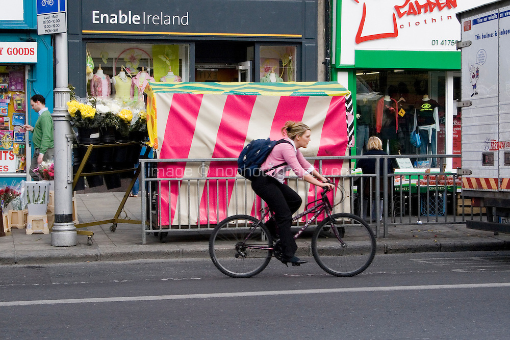 Cyclist in bus/cycle lane in Dublin Ireland street market vendors in background