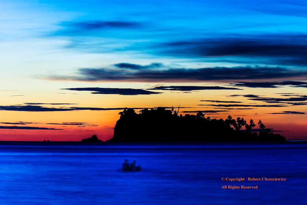 Goodnight Ko Chang: A pair of silhouetted swimmers frolics in the waves, saying goodnight under the waning light of the day, Lonely Beach - Ko Chang Thailand.