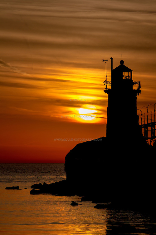 The setting sun creates a wintry silhouette of the frozen South Pier Lighthouse in South Haven