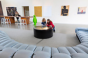 BENTONVILLE, AR - FEBRUARY 15:  Photographs Jessica Brown and her mother Kate Brown from Fayetteville, Arkansas playing with a art exhibit in the lobby showing the front desk and the art work that is displayed around the hotel along with the green Penguins watching over the hotel in Bentonville, Arkansas.<br /> CREDIT Wesley Hitt for The Wall Street Journal<br /> WALMART-Bentonville Scene-setters