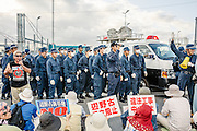 Protesters sing protest songs whilst police are deployed outside the main gate of Camp Schwab to manage the crowd. They come out in force when vehicles, often trucks carrying building material, are about to enter the US Military Base. Henoko, Okinawa, Japan.