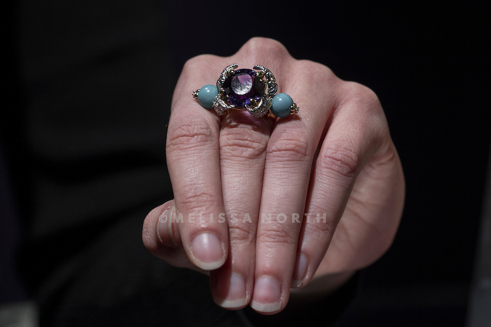 A member of staff at Bonhams models an anethyst turquoise and diamond ring by Jean Schlumberger, est £5,200 - 7,800, at a preview of the auction highlights from the Estate of Lauren Bacall, at Bonhams, London, UK on 13th February 2015. The preview of 50 selected lots features works by Henry Moore, David Hockney, Robert Graham, Noel Coward and Jim Dine - and is due to be auctioned at Bonhams New York on 31 March and 1 April 2015.