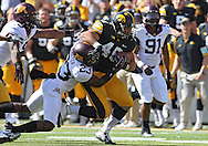 September 29 2012: Iowa Hawkeyes running back Mark Weisman (45) tries to push off Minnesota Golden Gophers defensive back Michael Carter (23) on a run during the first quarter of the NCAA football game between the Minnesota Golden Gophers and the Iowa Hawkeyes at Kinnick Stadium in Iowa City, Iowa on Saturday September 29, 2012. Iowa defeated Minnesota 31-13 to claim the Floyd of Rosedale Trophy.