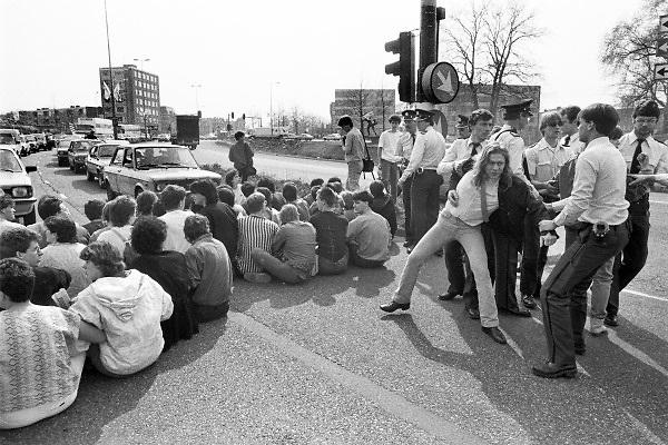 Nederland, Nijmegen, 1985Blokkade van het verkeer over het Trajanusplein. Studentenactie, studentenprotest, in de jaren 80 en begin 90 .Demonstratie van studenten tegen de wet op de studiefinanciering en hervormingen in het wetenschappelijk onderwijsdoor minister Deetman. Die kreeg te maken met grote demonstraties van studenten na de verhoging van de collegegelden en het verkorten van de studieduur.Foto: Flip Franssen