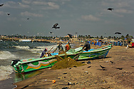 A group of man on the beach replacing their fish nets at the Negombo fish market. This fish market is the second largest fish market in Sri Lanka. It is situated near the Old Dutch Fort Gate and held every day except Sundays