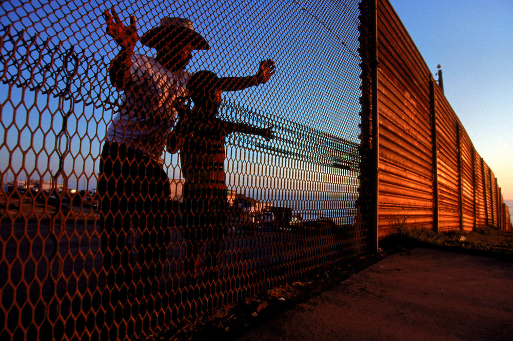 View from another world, a father and son peer through the international boundary into the United States from Tijuana, Mexico. Please contact Todd Bigelow directly with your licensing requests.
