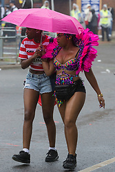 London, August 28th 2016. Two women make their way through the rain towards their rendezvous as Europe's biggest street party, the Notting Hill Carnival gets underway.