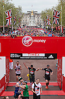 The mass of runners cross the finish line on The Mall with the Queen Victoria Memorial and Buckingham Palace in the background at the Virgin Money London Marathon, Sunday 26th April 2015.<br /> <br /> Dillon Bryden for Virgin Money London Marathon<br /> <br /> For more information please contact Penny Dain at pennyd@london-marathon.co.uk