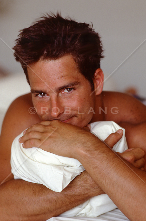sexy man hugging a pillow in bed
