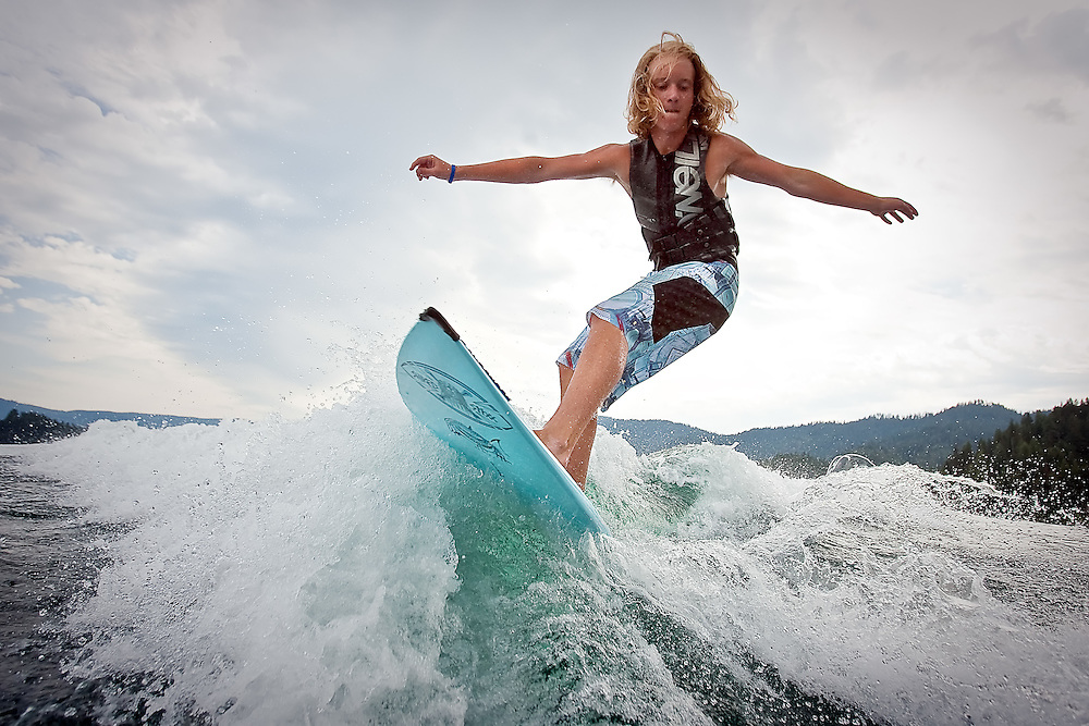 JEROME A. POLLOS/Press..Essex Prescott, 16, slices into a wake as he wake surfs Thursday on Hayden Lake. Prescott and two of his teenage friends started a wakeboarding instructional service two years ago and now have their summers booked with clients.