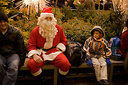 Santa takes a rest at the Channel Gardens in Rockefeller Center as a puzzled boy looks askance at him.