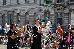 © Licensed to London News Pictures. 05/08/2018. LONDON, UK.  Gandini Juggling premiere a special commission, Cascade, accompanied by the rousing sound of brass music played live by Circus Tsuica, a French band of musical acrobats, in the fountains of the courtyard of Somerset House.  The performance is part of Circus Sampler, a selection of circus inspired events taking place Somerset House.  Photo credit: Stephen Chung/LNP