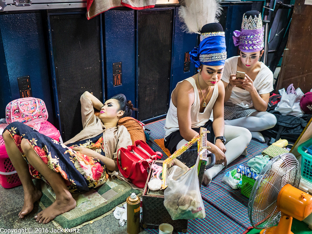 "30 JANUARY 2016 - NONTHABURI, NONTHABURI, THAILAND: Likay performers wait to go on stage during a ""likay"" show at Wat Bua Khwan in Nonthaburi, north of Bangkok. Likay is a form of popular folk theatre that includes exposition, singing and dancing in Thailand. It uses a combination of extravagant costumes and minimally equipped stages. Intentionally vague storylines means performances rely on actors' skills of improvisation. Like better the known Chinese Opera, which it resembles, Likay is performed mostly at temple fairs and privately sponsored events, especially in rural areas. Likay operas are televised and there is a market for bootleg likay videos and live performance of likay is becoming more rare.     PHOTO BY JACK KURTZ"