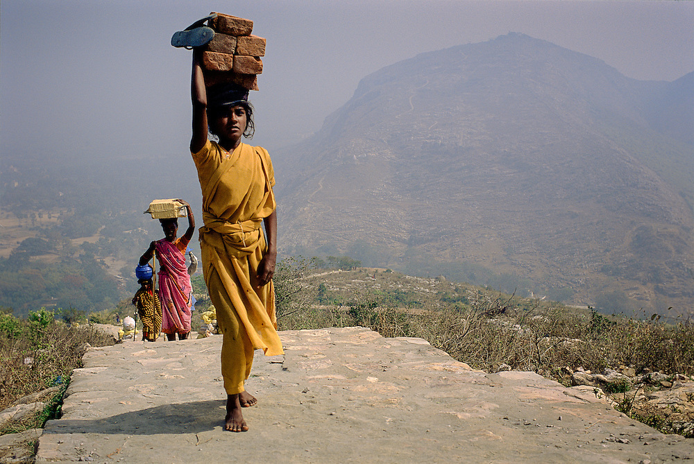 — Laborers of all ages spend the day carrying bricks to a building site for a temple at the top of a mountain in Nalanda.