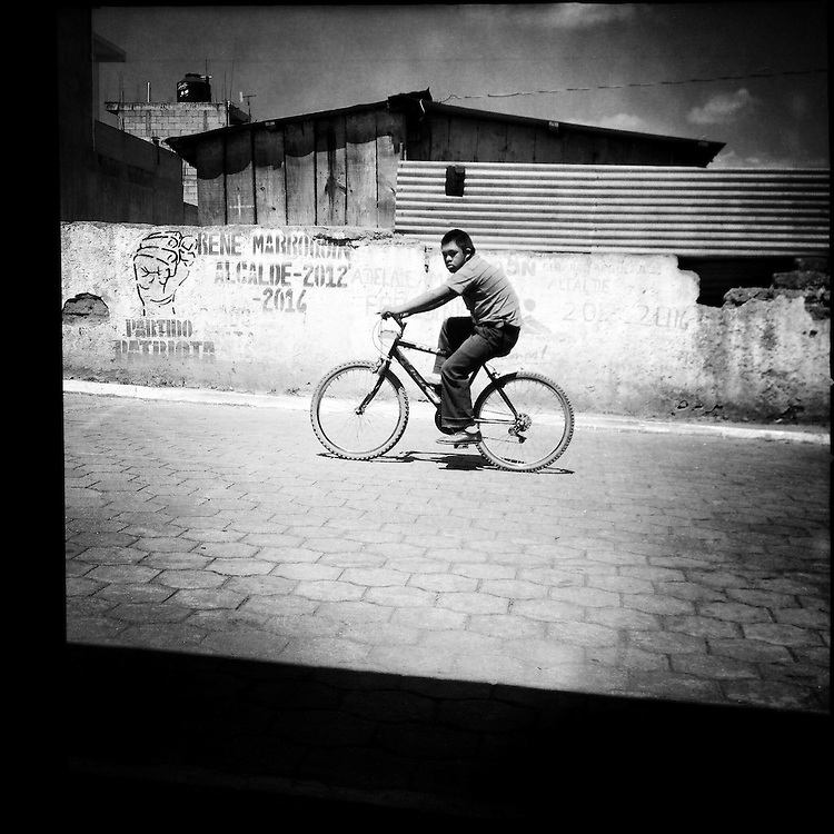 Teenager riding a bicycle. Rincón Grande, Zaragoza, Chimaltenango, Guatemala. February 27, 2014.