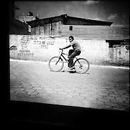 Teenager riding a bicycle. Rincón Grande, Zaragoza, Chimaltenango, Guatemala. February 27, 2014.