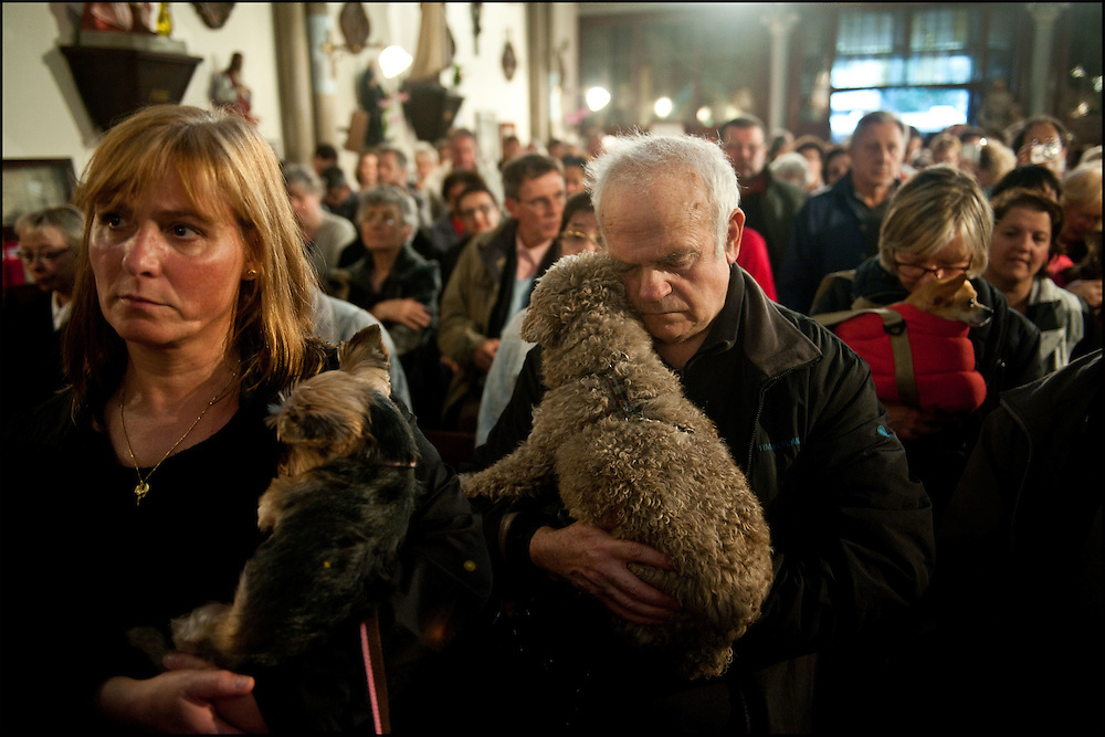 Des fideles en compagnie de leur animaux de compagnie ecoutent Monseigneur Dominique Philippe qui celebre une messe pontifical en l'eglise Sainte Rita et benit a cette occasion les animaux presents. A Paris le 6 novembre 2011. ©Benjamin Girette / IP3Press