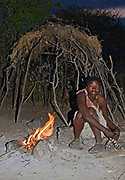 Hadzabe woman in front of her simple hut.  Lake Eyasi, northern Tanzania.