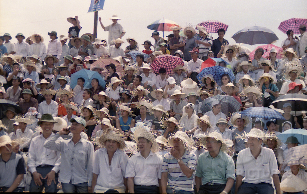 Spectators watch the buffalo fighting festival, Do Son, Vietnam, Asia. Most of them wears straw hats