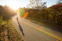 Man cycling, or road biking, on the Blue Ridge Parkway outside Roanoke, Virginia, at evening in fall color.