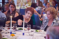 Marilyn Blackhall pours a first glass of wine for Vivian Crites.  The Hebrew Congregation of St. Thomas celebrate Passover Seder at Lillienfeld House with Rabbi Ron Herstik.  St. Thomas, USVI.  3 April 2015.  © Aisha-Zakiya Boyd
