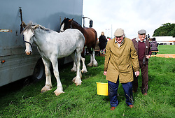 © Licensed to London News Pictures.26/08/15<br /> Egton, UK. <br /> <br /> Two men feed their horses at the 126th Egton Show in North Yorkshire. <br /> <br /> Egton is one of the largest village shows in the country and is run by a band of voluntary helpers. <br /> <br /> This year the event featured wrought iron and farrier displays, a farmers market, plus horse, cattle, sheep, goat, ferret, fur and feather classes. There was also bee keeping, produce and handicrafts on display.<br /> <br /> Photo credit : Ian Forsyth/LNP