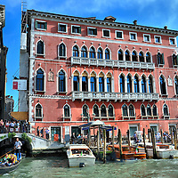 Palazzo Bembo on Grand Canal in Venice, Italy <br /> Another example of the Venetian Gothic architecture is the red façade of the Palazzo Bembo.  This palace on the Grand Canal was built in the 15th century and was the birthplace of Italian Cardinal Pietro Bembo who died in the mid-16th century.  It is now a highly rated hotel.  This location also hosts the Venice Biennale, which on a rotating two year basis is an exhibition for contemporary art, a film festival and architecture.