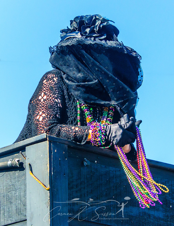 "One of Joe Cain's ""Merry Widows"" rides on their float as it travels down Washington Street in downtown Mobile, Ala., during the Joe Cain Procession at Mardi Gras, March 2, 2014. ""Cain's Merry Widows"" are a female-only mystic society formed in 1974. Each of the ""widows"" proclaims that Joe loved them best. Joe's mistresses also add to the light-hearted squabbling. French settlers held the first Mardi Gras in 1703, making Mobile's celebration the oldest Mardi Gras in the United States. (Photo by Carmen K. Sisson/Cloudybright)"