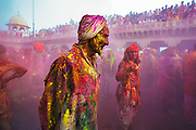 A kid looks at an old man covered in color while celebrating, Holi, 'the festival of colors' in Nand Gaon Village, near Mathura, India.<br /> <br /> People sit together and sing and abuse each other in braj language while others throw colored powder and water on them.