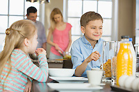 Siblings having breakfast at table with parents cooking in background