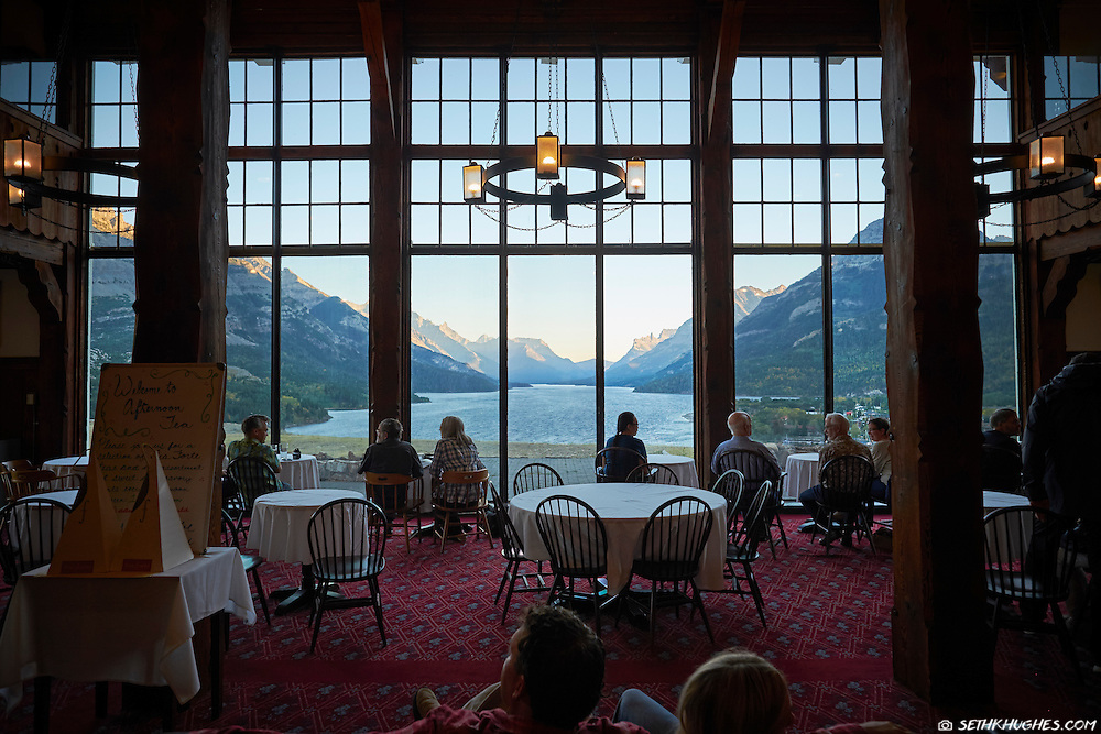 Guests of the Prince of Wales Hotel enjoy the view of Waterton Lake from the lobby in Waterton Lakes National Park, Alberta, Canada.