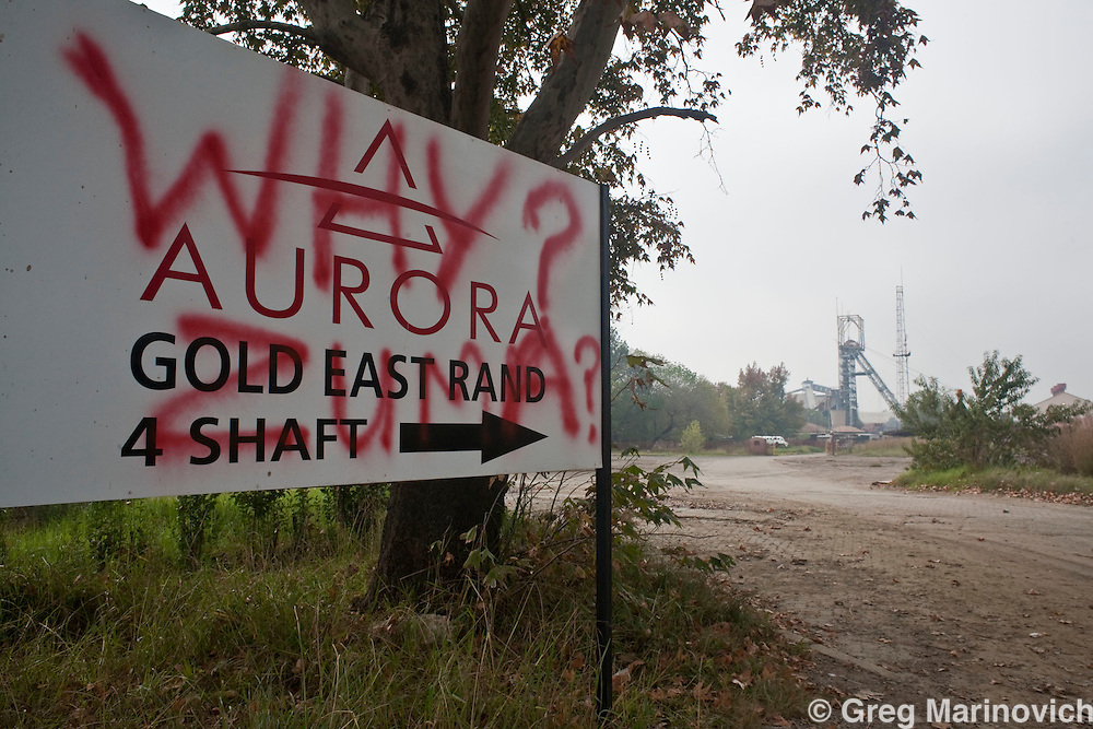 """An Aurora signboard with """"Why Zuma?"""" grafitti on it at grootveli mine. Fledgling gold-mining company Aurora Empowerment Systems is in crisis as it fails to pay workers at its Grootvlei gold mine for the third month. It is headed by former President Nelson Mandela's grandson Zondwe and President Jacob Zuma's nephew Kulubese Zuma.  The workers hostel has no water due to unpaid bills, and faeces clog the toilets, electricity is sporadic and the miners kitchen has been closed, despite a deduction being taken off for food services. Photo Greg Marinovich."""