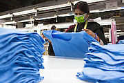 A women folds C & A T-shirts on a production line of Pratibha Syntax factory, where organic cotton is being used to make clothes.