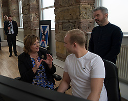 Culture Secretary Fiona Hyslop visits the studios of Blazing Griffin, a film & tv production and post production company, who have just received £200,000 GBP funding to enhance their facilities in Glasgow. She is pictured with Ross McRae and David Frew of Blazing Griffin, in one of the company's purpose built editing suites.<br /> <br /> © Dave Johnston/ EEm