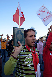© under license to London News Pictures. 19/02/2011. A man holds up a copy of the Qur'an during a march from Salmanyia Medical Complex to Pearl Roundabout in Manama, Bahrain today (19/02/2011).  Photo credit should read Michael Graae/London News Pictures