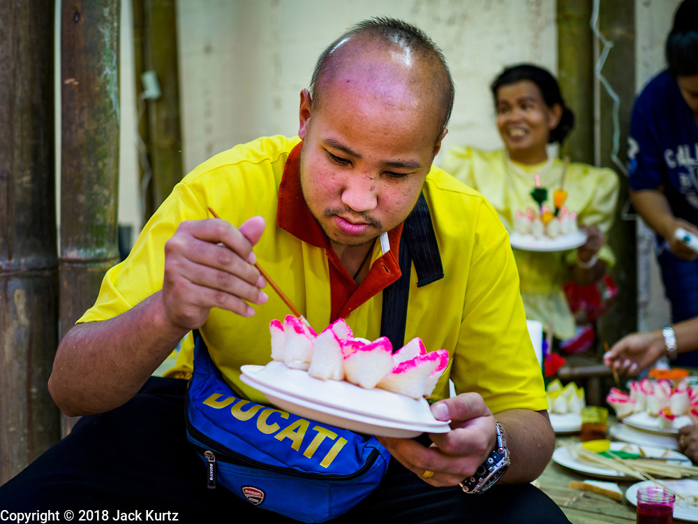 19 NOVEMBER 2018 - BANGKOK, THAILAND: A man makes a krathong out of bread during the Loy Krathong Fair along Klong (Canal) Ong Ang in Bangkok. This the first public event along the canal. Businesses that line the canal weve evicted about two years and the walkways along the canal were renovated. Loy Krathong takes place on the evening of the full moon of the 12th month in the traditional Thai lunar calendar. In the western calendar this usually falls in November. Loy means 'to float', while krathong refers to the usually lotus-shaped container which floats on the water. Traditional krathongs are made of the layers of the trunk of a banana tree or a spider lily plant. Now, many people use krathongs of baked bread which disintegrate in the water and feed the fish. A krathong is decorated with elaborately folded banana leaves, incense sticks, and a candle. A small coin is sometimes included as an offering to the river spirits. On the night of the full moon, Thais launch their krathong on a river, canal or a pond, making a wish as they do so. The krathongs made at the Klong Ong Ang fair were made out of bread so they would decompose and feed the fish in the canal. Loy Krathong will be celebrated on November 22 this year.    PHOTO BY JACK KURTZ