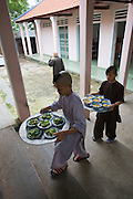 Thien Mu Pagoda. Young novices bringing food for the other monks from the kitchen.