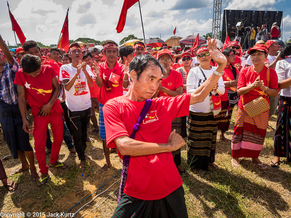 01 NOVEMBER 2015 - YANGON, MYANMAR: A man dances while people wait for Aung San Suu Kyi at the NLD's last election rally of the 2015  election in the Yangon suburbs Sunday. Political parties are wrapping up their campaigns in Myanmar (Burma). National elections are scheduled for Sunday Nov. 8. The two principal parties are the National League for Democracy (NLD), the party of democracy icon and Nobel Peace Prize winner Aung San Suu Kyi, and the ruling Union Solidarity and Development Party (USDP), led by incumbent President Thein Sein. There are more than 30 parties campaigning for national and local offices.    PHOTO BY JACK KURTZ