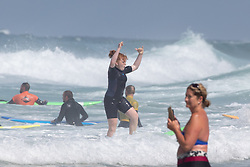 © Licensed to London News Pictures. 31/07/2020. Newquay, UK. A beginner surfer reacts after catching a wave on Fistral Beach, Cornwall, on a very hot day in the southwest. Parts of the country are expected to have the hottest day of the year so far. Photo credit : Tom Nicholson/LNP