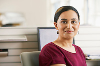 Mid-adult female office worker sitting in cubicle portrait