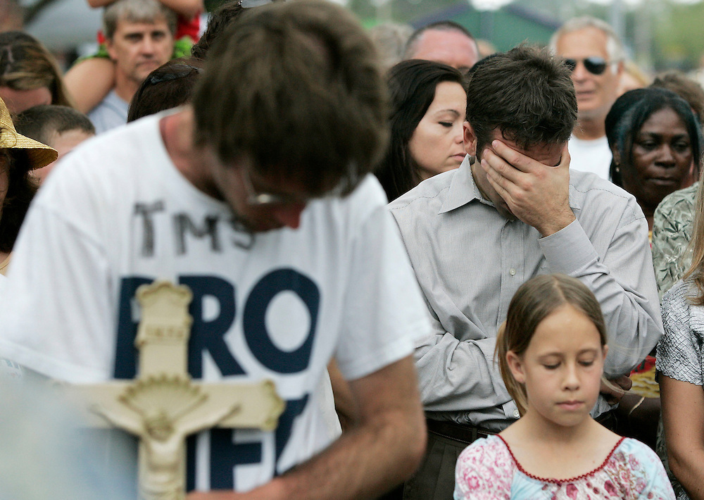 Bob Schindler, Jr. (R), brother of the brain damaged Terri Schiavo, holds his head while praying during an easter mass outside the Woodside Hospice where his sister Terri Schiavo  lay without a feeding tube in Pinellas Park, Florida on March 27, 2005. REUTERS/Scott Audette
