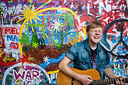 Tomas, a young guitar player in front of the Prague Lennon Wall. The Lennon Wall or John Lennon Wall, is a wall in Prague, Czech Republic. Once a normal wall, since the 1980s it has been filled with John Lennon-inspired graffiti and pieces of lyrics from Beatles songs.