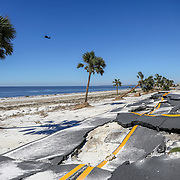 A helicopter flies along the coast as a portion of Highway 98 is seen crumbled Friday, Oct. 12, 2018 in Mexico Beach. Residents of the small beach town of Mexico Beach began to make their way back to their homes some for the first time after Hurricane Michael made landfall Wednesday.